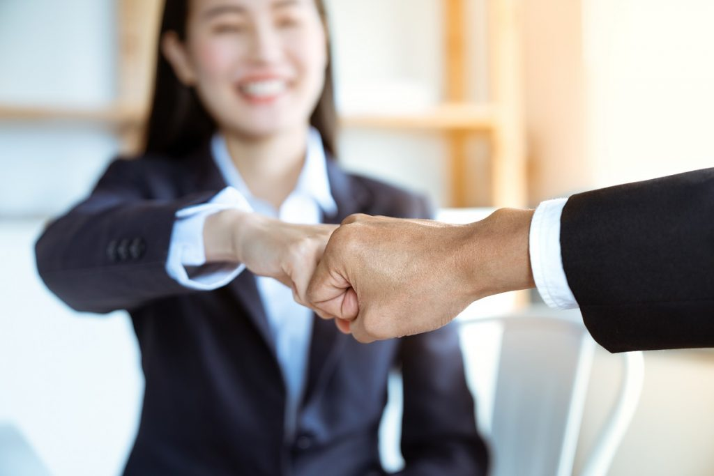 Smiling Asian Young Businesswoman Bump Fists With Her Boss After